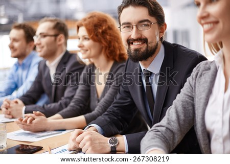 Young businessman sitting among co-workers and looking at camera at conference - stock photo
