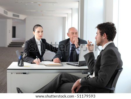 Young businessman sitting and talking to other business people - stock photo