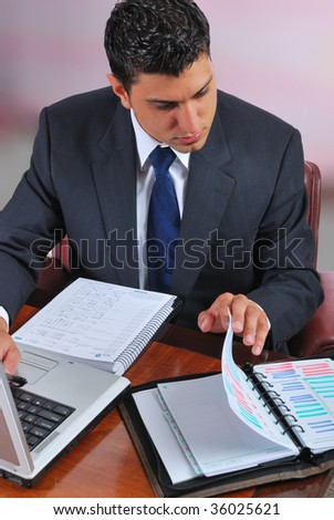 young businessman sitting at a desk, working on a laptop, looking through a personal organizer - stock photo
