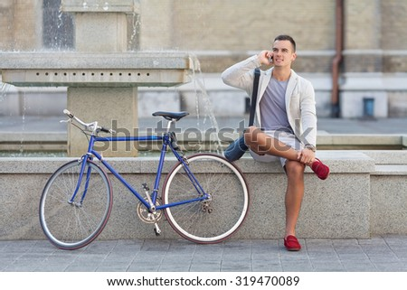 Young businessman sitting at a fountain and talking on the phone with his bicycle beside him - stock photo