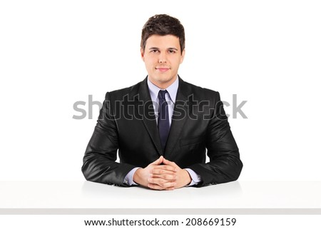 Young businessman sitting at a table isolated on white background - stock photo