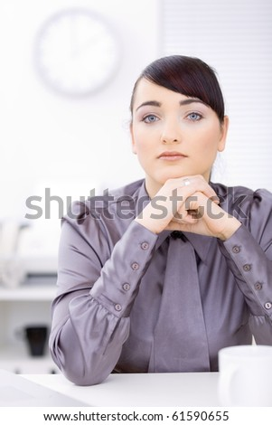 Young businessman sitting at desk at office, thinking.