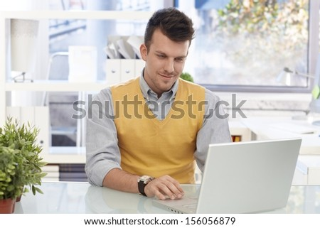 Young businessman sitting at desk in bright office, working with laptop computer, smiling. - stock photo