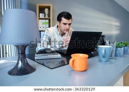 Young businessman sitting at desk, using laptop computer, thinking. - stock photo
