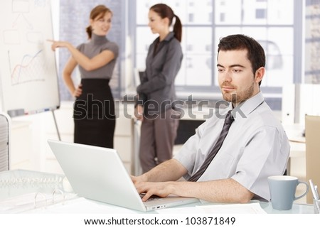 Young businessman sitting at desk, working on laptop, businesswomen standing by whiteboard, discussing diagrams in the background. - stock photo