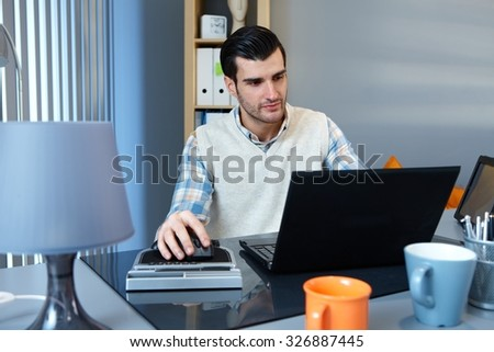 Young businessman sitting at desk, working with laptop computer, concentrating. - stock photo