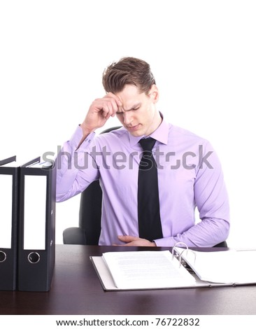 young businessman sitting at his desk having headache, isolated on white