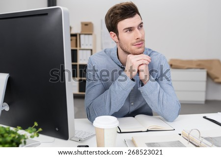 Young businessman sitting at his desk in the office thinking with his chin resting on his hands as he stares off to the side - stock photo