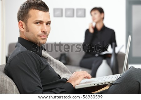 Young businessman sitting at office lobby working with laptop computer. - stock photo