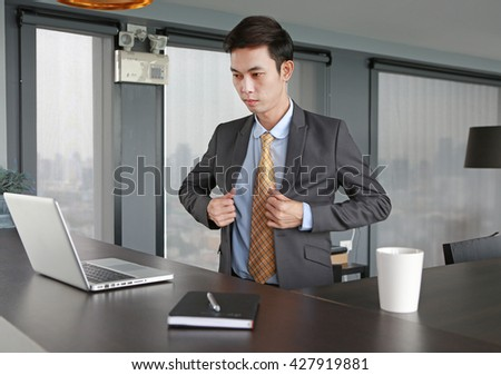 Young businessman sitting at the table and wearing suit - stock photo