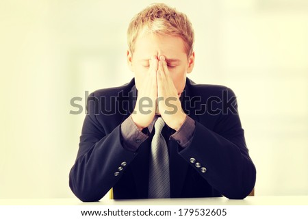 Young businessman sitting behind the desk and being worried - stock photo