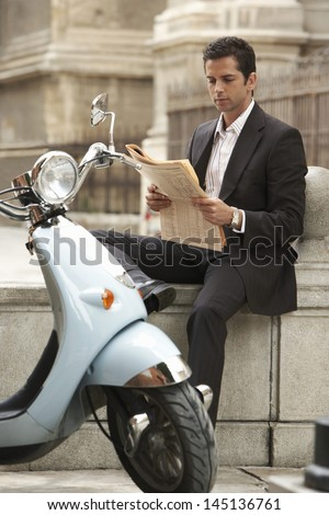 Young businessman sitting by scooter reading newspaper
