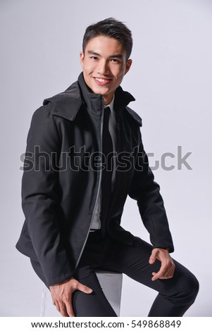 young businessman sitting cube on gray background