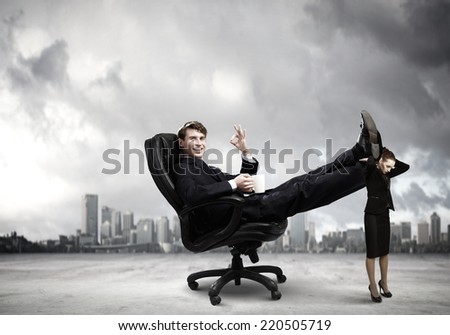 Young businessman sitting gin chair with legs on colleagues shoulders - stock photo