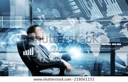 Young businessman sitting in chair behind media screen - stock photo