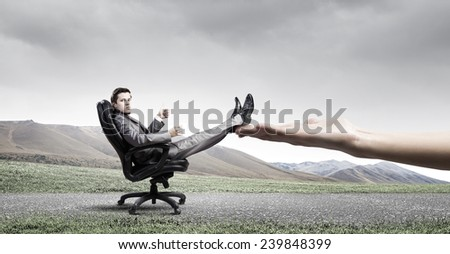 Young businessman sitting in chair with cup in hands
