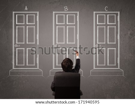 Young businessman sitting in front of a chalkboard and trying to choose the right door