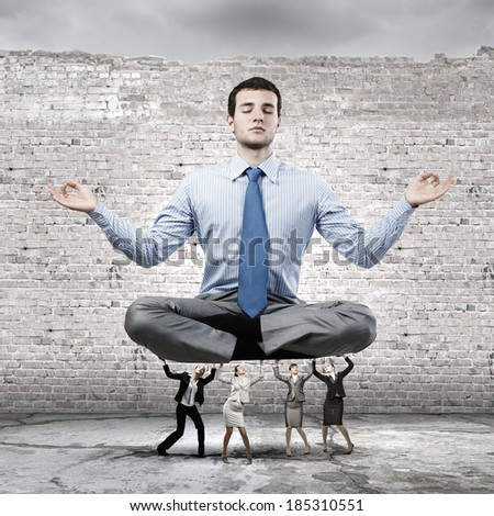Young businessman sitting in lotus pose and supported by colleagues - stock photo
