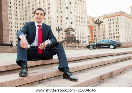 Young businessman sitting in modern downtown - stock photo