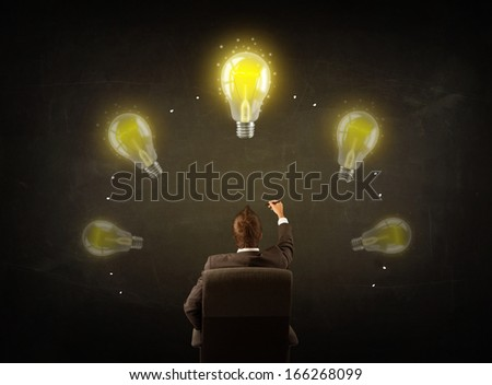 Young businessman sitting in office chair in front of a balckboard with glowing lightbulbs over his head