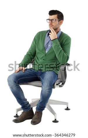 Young businessman sitting in swivel chair over white background, looking away, thinking. Full size. - stock photo