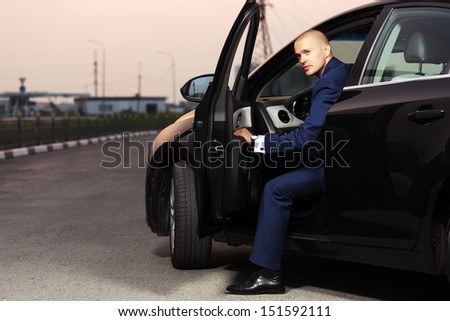 Young businessman sitting in the car - stock photo