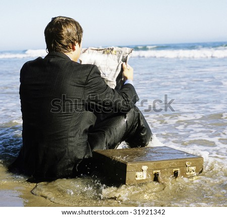Young businessman sitting in the ocean in a suit.