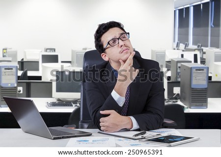 Young businessman sitting in the office while working on desk and thinking a solution