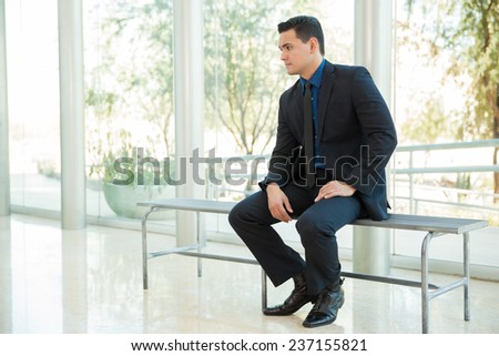 Young businessman sitting on a bench and waiting his turn for a job interview - stock photo