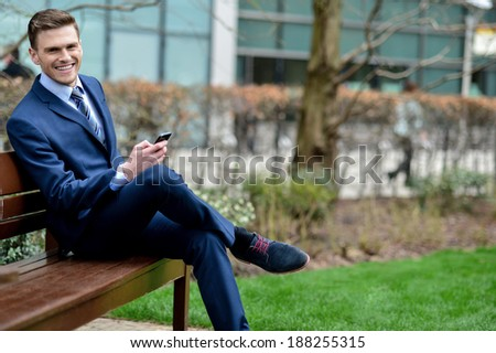 Young businessman sitting on a bench using his cell phone - stock photo