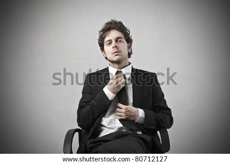Young businessman sitting on a chair - stock photo