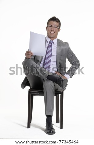 Young businessman sitting on a chair and holding a document on white background. - stock photo