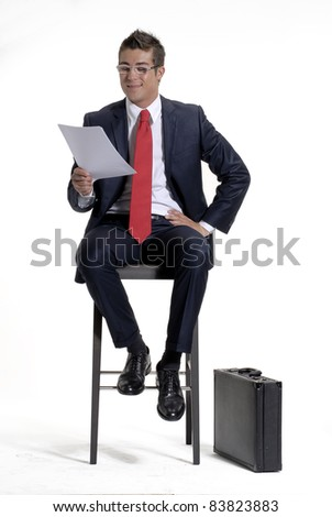 Young businessman sitting on a chair and reading on white background. - stock photo