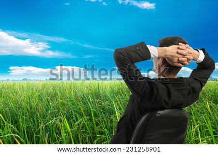 Young businessman sitting on a chair in front of a field of grass and look up at the sky. Vacation work - stock photo