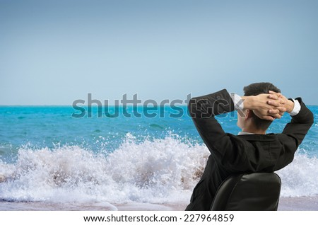 Young businessman sitting on a chair in front of the sea and looking up at the sky. Vacation work - stock photo