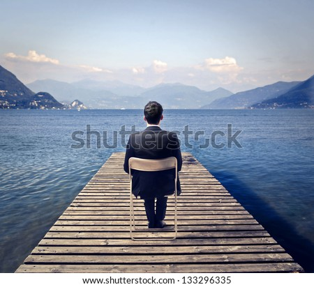 young businessman sitting on a chair looks the lake - stock photo