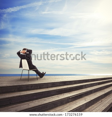 young businessman sitting on a chair looks the sea - stock photo