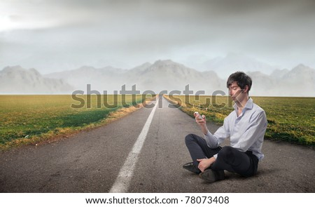 Young businessman sitting on a countryside road and using a mobile phone