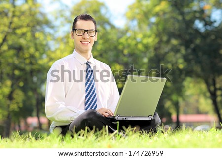 Young businessman sitting on a grass and working on a laptop in a park