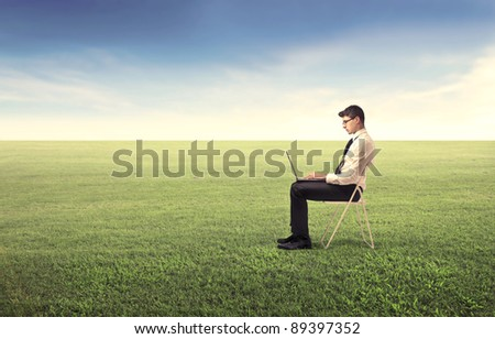 Young businessman sitting on a green meadow and using a laptop