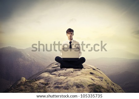 Young businessman sitting on a hill and using a laptop - stock photo