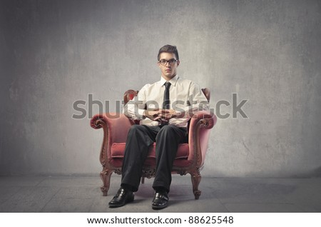 Young businessman sitting on an armchair - stock photo
