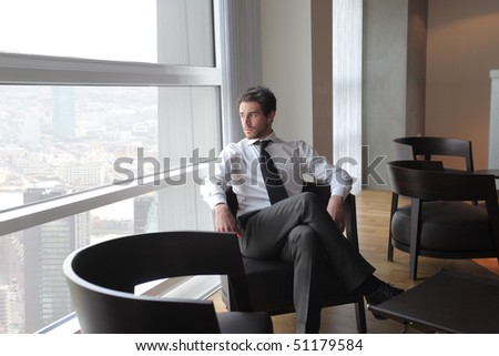 Young businessman sitting on an armchair in an office