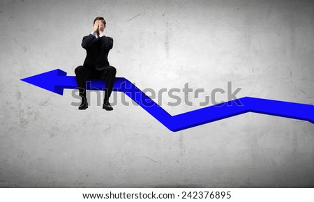 Young businessman sitting on arrow with closed eyes - stock photo