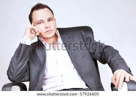 Young businessman sitting on chair and thinking.