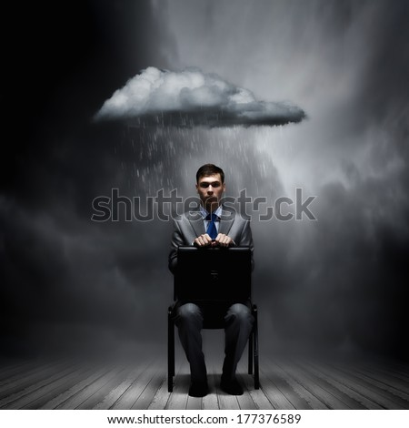 Young businessman sitting on chair with suitcase on knees - stock photo