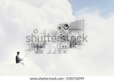 Young businessman sitting on cloud with mobile phone in hand - stock photo