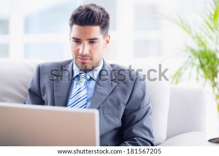 Young businessman sitting on couch using his laptop in the office - stock photo