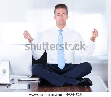 Young Businessman Sitting On Desk Practicing Yoga In Office - stock photo