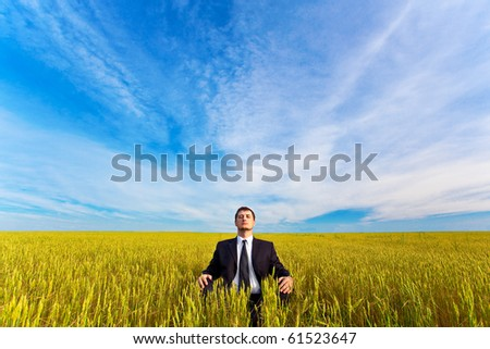 young businessman sitting on field - stock photo